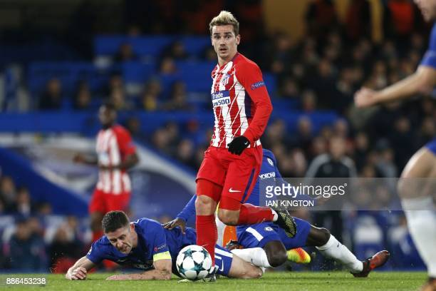 Atletico Madrid's French striker Antoine Griezmann vies with Chelsea's English defender Gary Cahill and Chelsea's French midfielder N'Golo Kante...