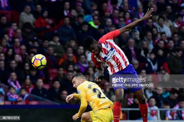 Atletico Madrid's Ghanaian midfielder Thomas heads the ball over Girona's Spanish midfielder Borja Garcia during the Spanish league football match...
