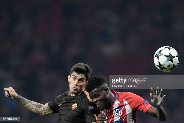 Atletico Madrid's Ghanaian midfielder Thomas heads the ball with Roma's Argentinian midfielder Diego Perotti during the UEFA Champions League group C...