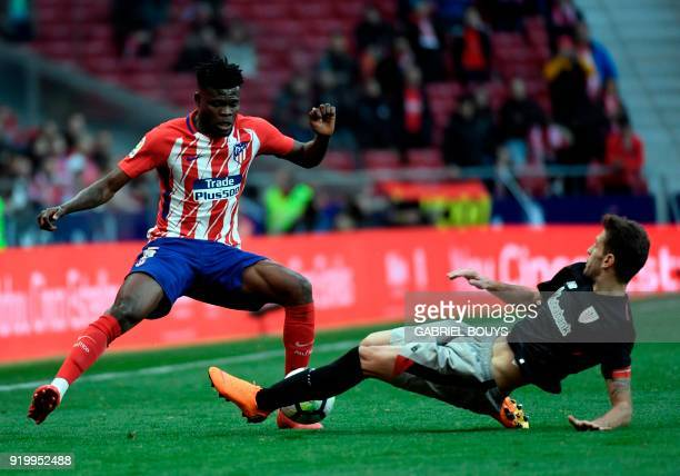Atletico Madrid's Ghanaian midfielder Thomas is tackled by Athletic Bilbao's Spanish defender Enric Saborit during the Spanish league football match...