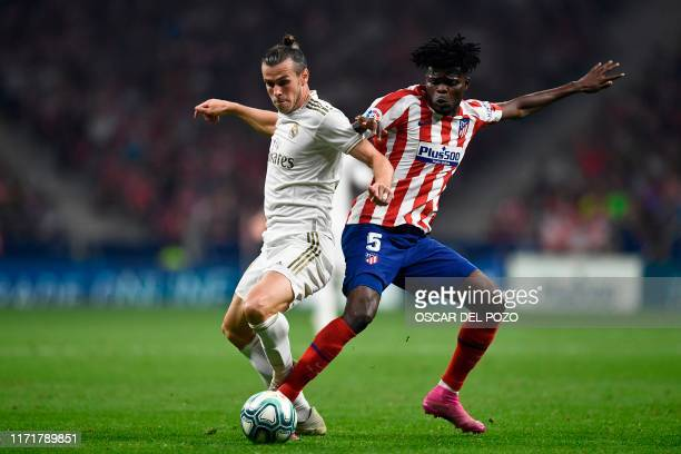 Atletico Madrid's Ghanaian midfielder Thomas Partey challeges Real Madrid's Welsh forward Gareth Bale during the Spanish league football match...