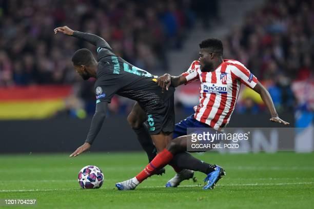 Atletico Madrid's Ghanaian midfielder Thomas Partey challenges Liverpool's Dutch midfielder Georginio Wijnaldum during the UEFA Champions League,...
