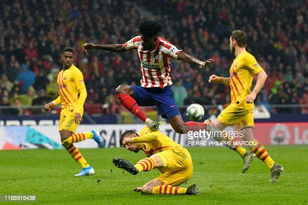 Atletico Madrid's Ghanaian midfielder Thomas Partey jumps over Barcelona's French defender Clement Lenglet during the Spanish league football match...