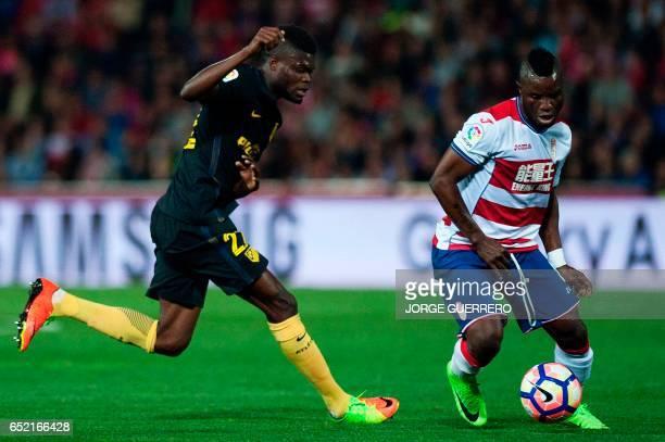 Atletico Madrid's Ghanaian midfielder Thomas Partey vies with Granada's Ghanaian midfielder Wakaso Mubarak during the Spanish league football match...