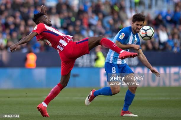 Atletico Madrid's Ghanaian midfielder Thomas vies with Malaga's midfielder Adrian Gonzalez during the Spanish league football match between Malaga CF...