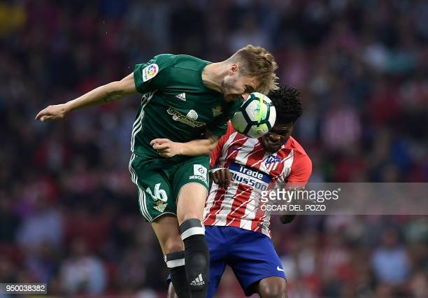 Atletico Madrid's Ghananian midfielder Thomas vies with Real Betis' Spanish forward Loren Moron during the Spanish league football match between Club...