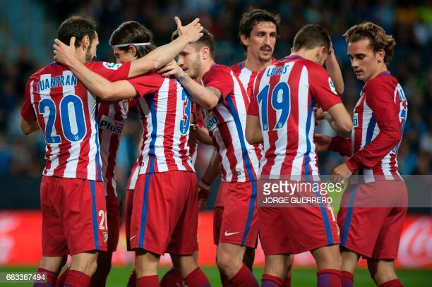 Atletico Madrid's Italian defender Filipe Luis celebrates a goal with teammates during the Spanish league football match Malaga CF vs Club Atletico...
