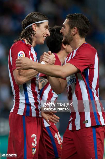 Atletico Madrid's Italian defender Filipe Luis celebrates with midfielder Koke after scoring during the Spanish league football match Malaga CF vs...