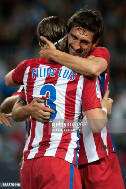 Atletico Madrid's Italian defender Filipe Luis celebrates with Atletico Madrid's Montenegrin defender Stefan Savic after scoring during the Spanish...
