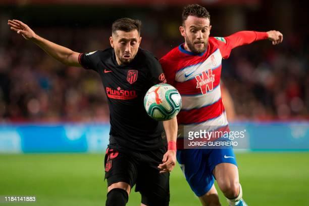 Atletico Madrid's Mexican defender Hector Herrera vies with Granada's Spanish defender Quini Marin during the Spanish league football match Granada...