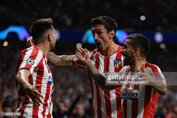 Atletico Madrid's Mexican midfielder Hector Herrera celebrates with Atletico Madrid's Montenegrin defender Stefan Savic and Atletico Madrid's...