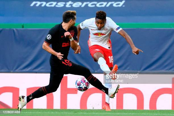 Atletico Madrid's Mexican midfielder Hector Herrera vies with Leipzig's French midfielder Christopher Nkunku during the UEFA Champions League...