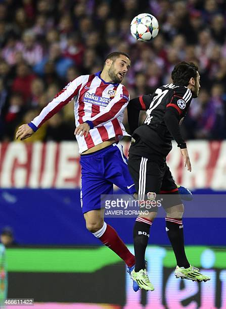 Atletico Madrid's midfielder Cani vies with Leverkusen's midfielder Hakan Calhanoglu during the UEFA Champions League football match Club Atletico de...