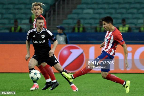 Atletico Madrid's midfielder from Argentina Nico Gaitan kicks the ball past Qarabag's defender from Azerbaijan Gara Garayev and Atletico Madrid's...