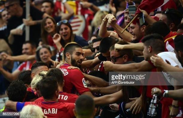 Atletico Madrid's midfielder from Belgium Yannick FerreiraCarrasco celebrates a goal with fans during the Spanish league football match Club Atletico...