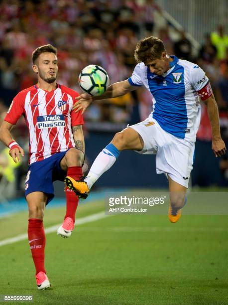 Atletico Madrid's midfielder from Spain Saul Niguez vies with Leganes' midfielder from Argentina Alexander Szymanowski during the Spanish league...