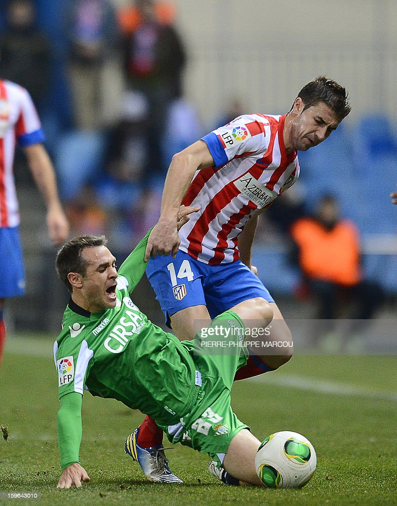 Atletico Madrid's midfielder Gabi (R) vies with Betis' defender Nacho during the Spanish Copa del Rey (King's Cup) quarter-final first leg football match Club Atletico de Madrid vs Real Betis at the Vicente Calderon stadium in Madrid on January 17, 2013.