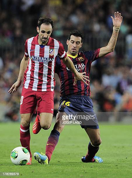 Atletico Madrid's midfielder Juanfran vies with Barcelona's midfielder Sergio Busquets during the Spanish Super Cup second leg football match FC...