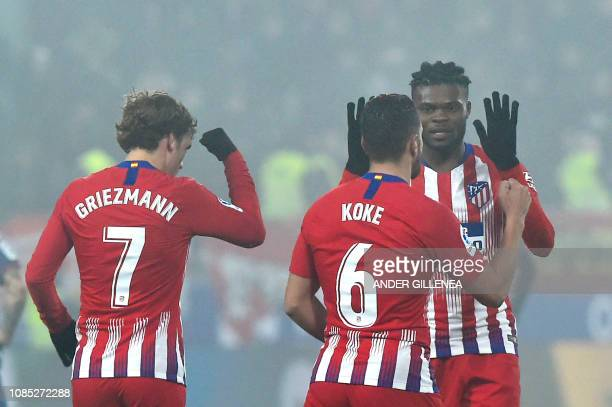 Atletico Madrid's midfielder Koke celebrates with Atletico Madrid's French forward Antoine Griezmann and Atletico Madrid's Ghanaian midfielder Thomas...