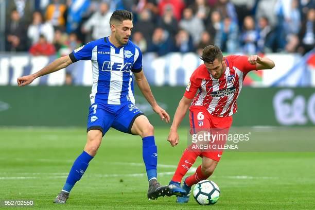 Atletico Madrid's midfielder Koke challenges Alaves' Spanish forward Ruben Sobrino during the Spanish league football match Deportivo Alaves vs...