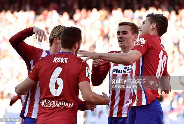 Atletico Madrid's midfielder Koke is congratulated by his teammates after scoring during the Spanish league football match Atletico de Madrid vs...