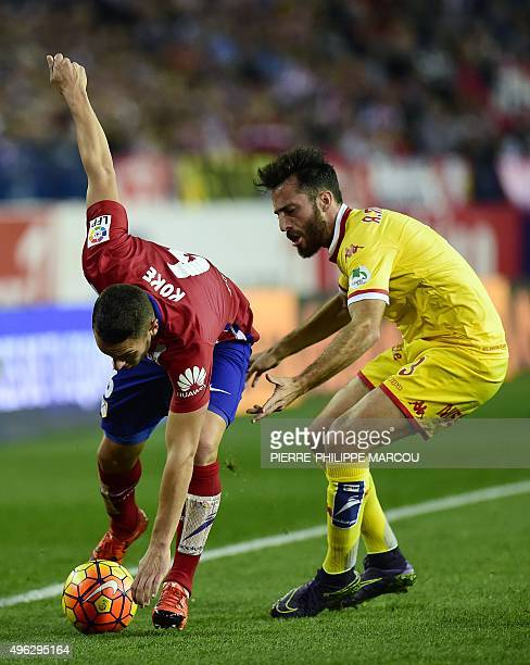 Atletico Madrid's midfielder Koke vies with Sporting Gijon's defender Alex Menendez during the Spanish league football match Club Atletico de Madrid...