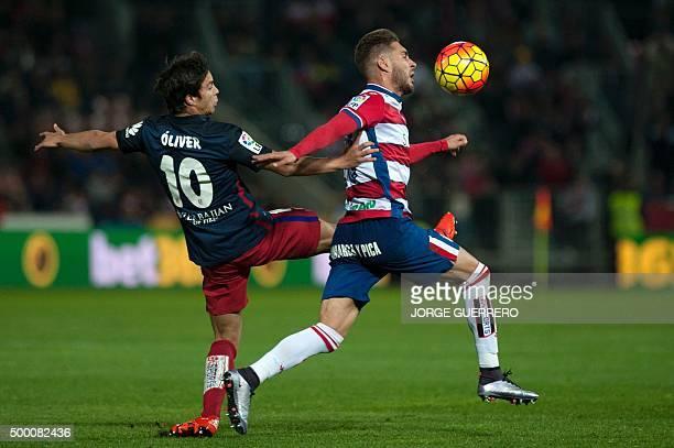 Atletico Madrid's midfielder Oliver Torres vies with Granada's forward Ruben Rochina during the Spanish league football match Granada FC VS Club...