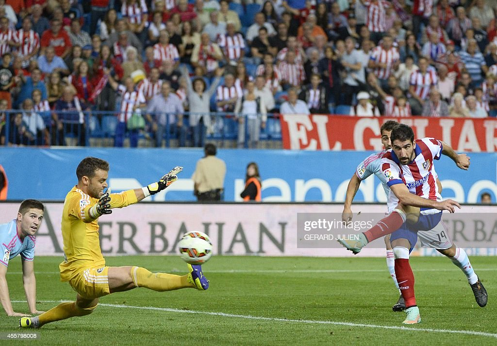 Atletico Madrid's midfielder Raul Garcia (R) shoots past Celta Vigo's goalkeeper Sergio Alvarez during the Spanish league football match Club Atletico de Madrid vs Celta de Vigo at the Vicente Calderon stadium in Madrid on September 20, 2014. The game ended in a draw 2-2.