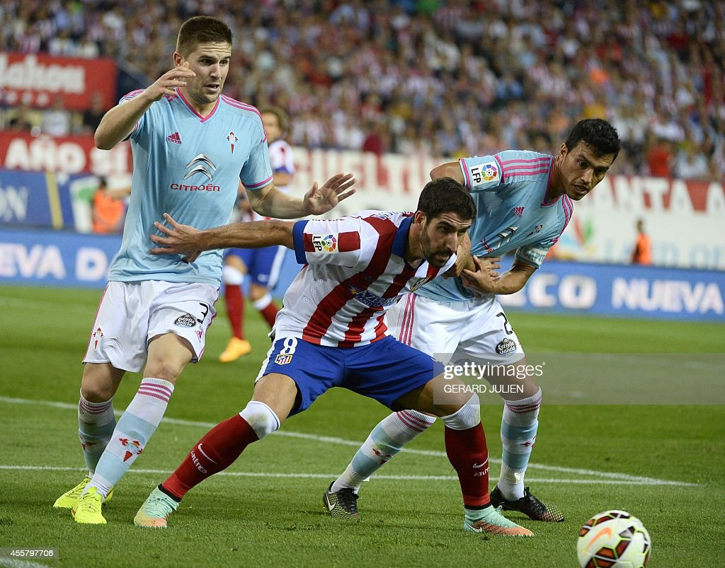 Atletico Madrid's midfielder Raul Garcia (C) vies with Celta Vigo's defender Andreu Fontas (L) and Celta Vigo's Argentinian defender Gustavo Cabral during the Spanish league football match Club Atletico de Madrid vs Celta de Vigo at the Vicente Calderon stadium in Madrid on September 20, 2014. The game ended in a draw 2-2.