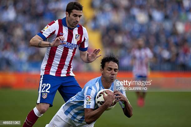 "Atletico Madrid's midfielder Ruben Gracia Calmache ""Cani"" vies with Malaga's Brazilian defender Weligton during the Spanish league football match..."