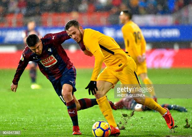 Atletico Madrid's midfielder Saul Niguez vies with Eibar's Spanish midfielder Ander Capa during the Spanish league football match between SD Eibar...