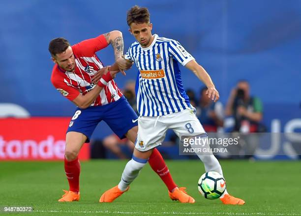 Atletico Madrid's midfielder Saul Niguez vies with Real Sociedad's Belgian midfielder Adnan Januzaj during the Spanish league football between Real...