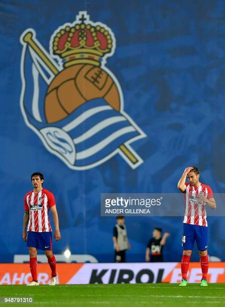 Atletico Madrid's Montenegrin defender Stefan Savic and Atletico Madrid's Spanish midfielder Gabi stand on the field after Real Sociedad scored the...