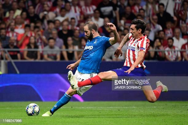 TOPSHOT Atletico Madrid's Montenegrin defender Stefan Savic challenges Juventus' Argentinian forward Gonzalo Higuain during the UEFA Champions League...