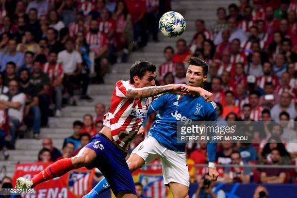 Atletico Madrid's Montenegrin defender Stefan Savic vies with Juventus' Portuguese forward Cristiano Ronaldo during the UEFA Champions League Group D...
