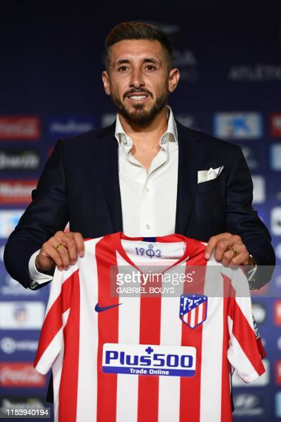 Atletico Madrid's new Mexican midfielder Hector Herrera holds his new jersey during his official presentation by the Spanish football club at the...