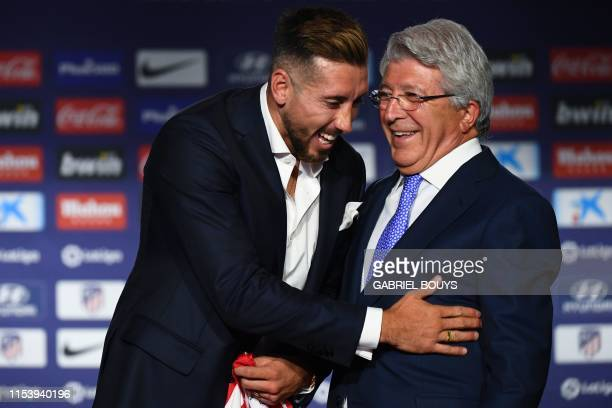 Atletico Madrid's new Mexican midfielder Hector Herrera jokes with the Spanish football club's president Enrique Cerezo during his official...
