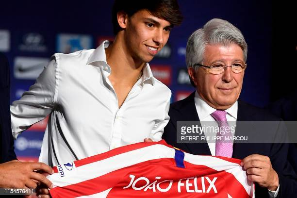 Atletico Madrid's new Portuguese midfielder Joao Felix holds his new jersey next to the Spanish football club's president Enrique Cerezo during his...