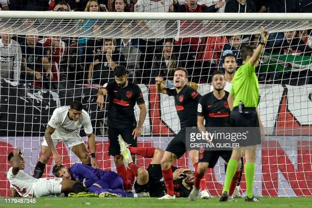 Atletico Madrid's players argue with the referee during the Spanish League football match between Sevilla FC and Club Atletico de Madrid at the Ramon...