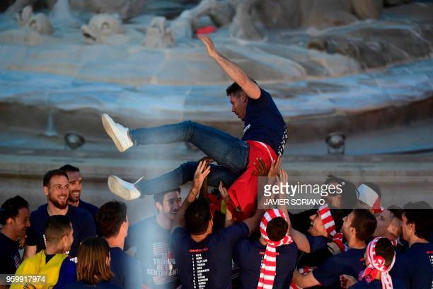 Atletico Madrid's players carry Atletico Madrid's Argentinian coach Diego Simeone during a parade celebrating their Europa League victory at the...