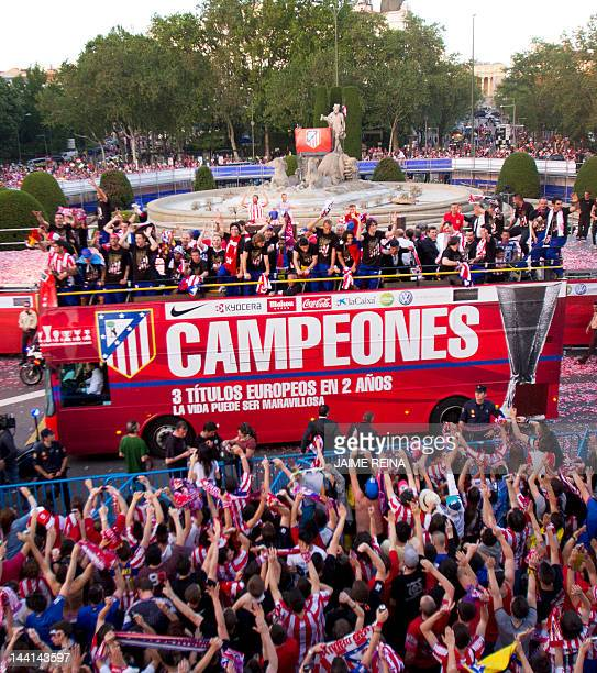 Atletico Madrid's players celebrate with supporters at the Neptuno square in Madrid on May 10 after their win over fellow Spaniards Athletic Bilbao...