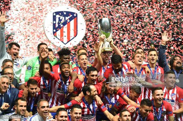 TOPSHOT Atletico Madrid's players celebrate with the trophy after winning the UEFA Super Cup football match Atletico de Madrid vs Real Madrid CF at...