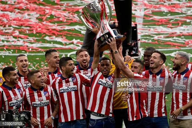Atletico Madrid´s players celebrate with the trophy at the Wanda Metropolitano stadium in Madrid on May 23, 2021 after winning the Spanish Liga...