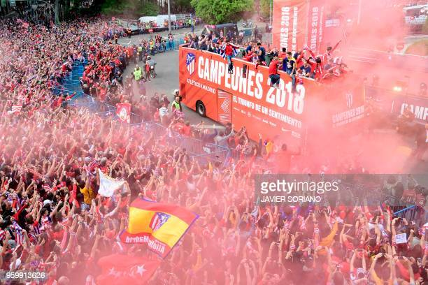 TOPSHOT Atletico Madrid's players parade aboard an opentop bus to celebrate their Europa League victory at the Fountain of Neptune in Madrid on May...