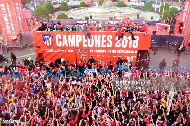 Atletico Madrid's players parade aboard an opentop bus to celebrate their Europa League victory at the Fountain of Neptune in Madrid on May 18 2018