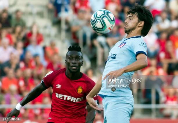 Atletico Madrid's Portuguese forward Joao Felix controls the ball beside Mallorca's Ghanaian midfielder Iddrisu Baba during the Spanish league...
