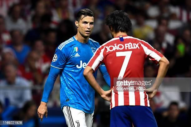 Atletico Madrid's Portuguese forward Joao Felix speaks with Juventus' Portuguese forward Cristiano Ronaldo during the UEFA Champions League Group D...