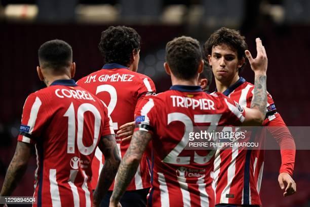 Atletico Madrid's Portuguese midfielder Joao Felix celebrates with Atletico Madrid's English defender Kieran Trippier after scoring during the UEFA...