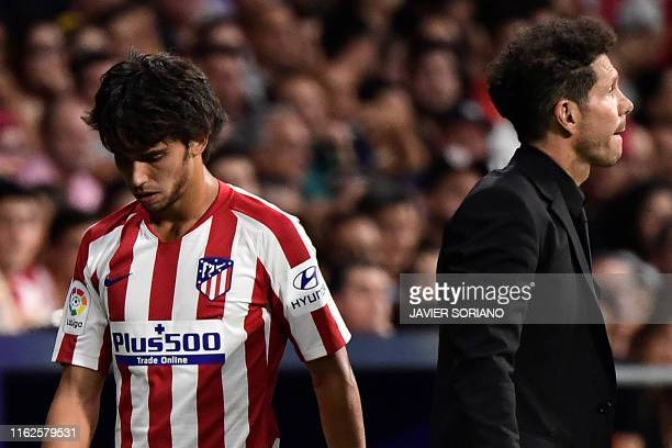 Atletico Madrid's Portuguese midfielder Joao Felix walks past Atletico Madrid's Argentinian coach Diego Simeone as he leaves the pitch after getting...