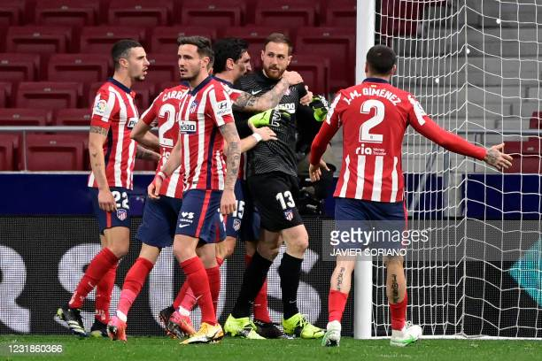 Atletico Madrid's Slovenian goalkeeper Jan Oblak celebrates with teammates after stopping a penalty kick during the Spanish League football match...